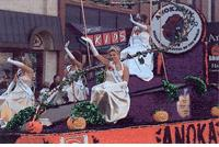 A Halloween Parade Float with a Lady in a White Dress Riding It